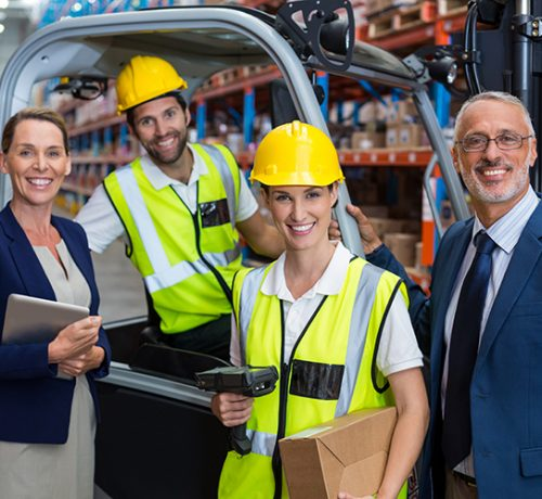 Warehouse manager and client standing with co-workers in warehouse